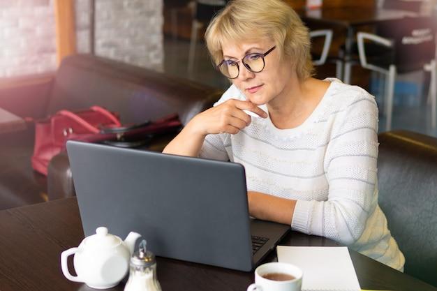 Femme avec un ordinateur portable travaille dans un café au bureau, elle est pigiste.