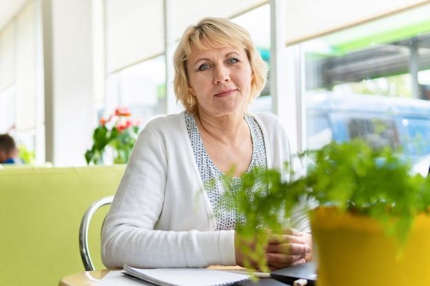 Une femme avec un ordinateur portable travaille dans un café au bureau, elle est pigiste