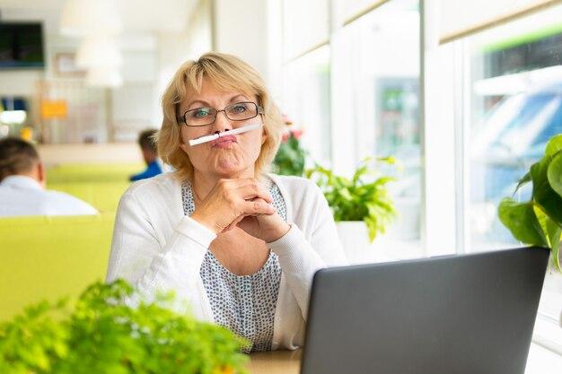 Une femme avec un ordinateur portable travaille dans un café au bureau