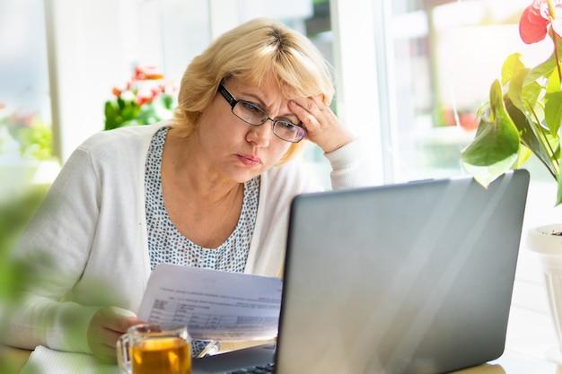 Une femme avec un ordinateur portable travaille dans un café