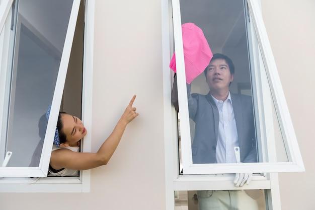 Femme ordre mari à nettoyer la fenêtre de la maison