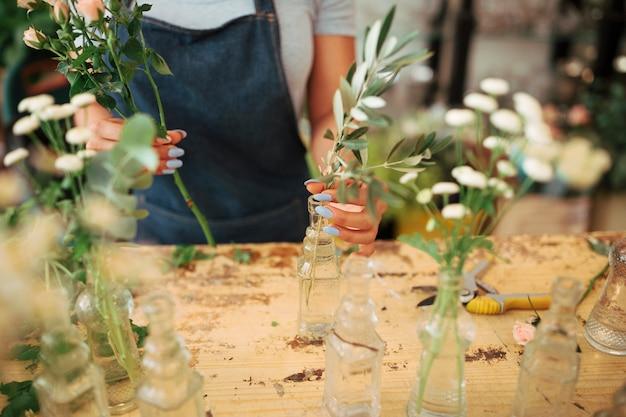 Femme organisant des plantes dans un vase en verre