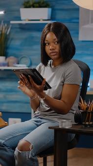 Femme d'origine afro-américaine tenant une tablette numérique
