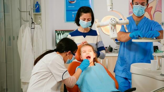 Femme orthodontiste allumant la lampe examinant un petit patient à l'aide d'outils dentaires stériles dans une clinique stomatologique. docteur en dentisterie parlant à un enfant assis sur une chaise stomatologique, fille ouvrant la bouche