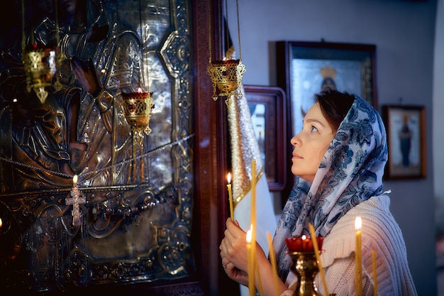 Femme orthodoxe priant devant des icônes dans l'église