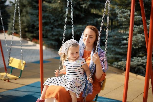 Femme orthodoxe russe sur une balançoire avec une petite fille