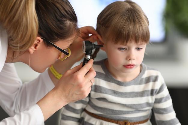 Femme oto-rhino-laryngologiste examine l'oreille de la petite fille avec otoscope en clinique