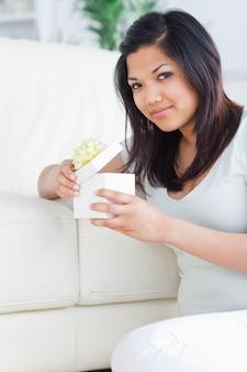Femme ouvrant une boîte-cadeau tout en étant assis sur le sol devant un canapé