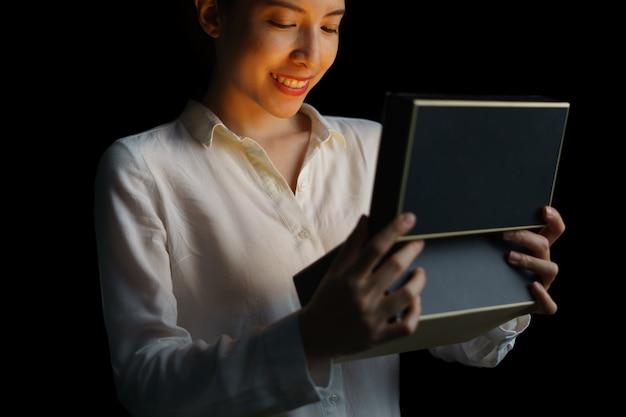 Une femme ouvrant une boîte avec une lumière dorée signifie quelque chose d'excitant à l'intérieur.