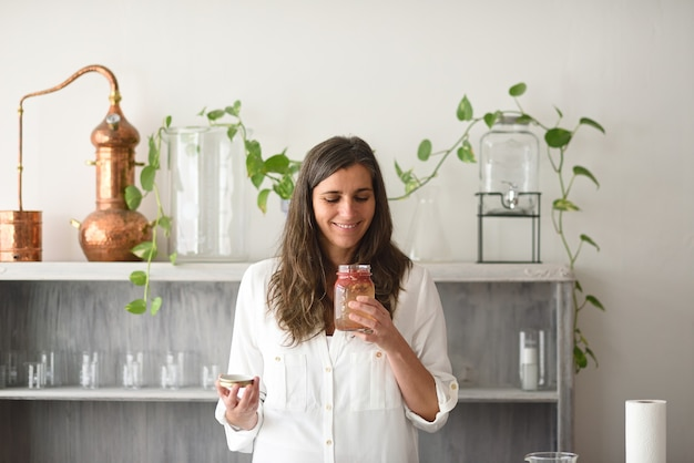 Femme ouvrant la bouteille d'élixir aromatique à base de plantes médicinales