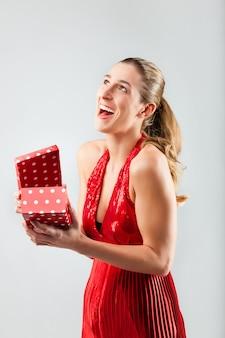 Femme ouvrant le cadeau et est heureuse