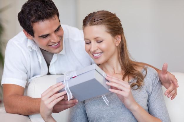 Femme ouvrant le cadeau qu'elle a reçu de son petit ami