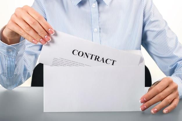 Femme ouvrant l'enveloppe avec contrat. la femelle ouvre l'enveloppe avec le contrat. le courrier frais est ici. gardez les doigts croisés.