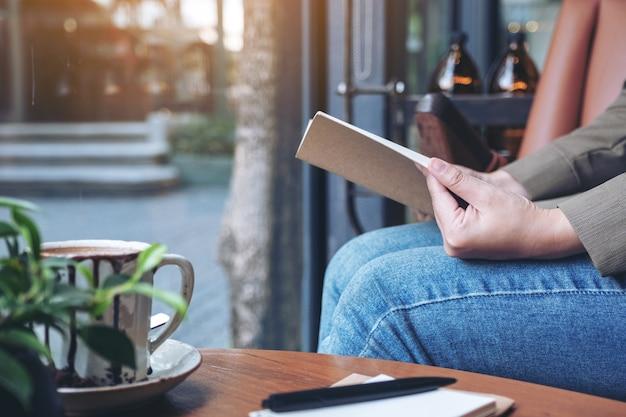 Femme ouvrant un livre avec des cahiers et une tasse de café sur une table en bois au café