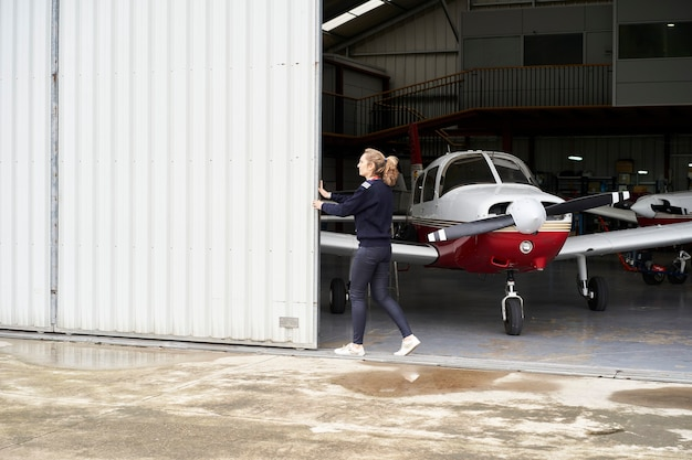 Femme ouvrant la porte du hangar où il y a plusieurs avions