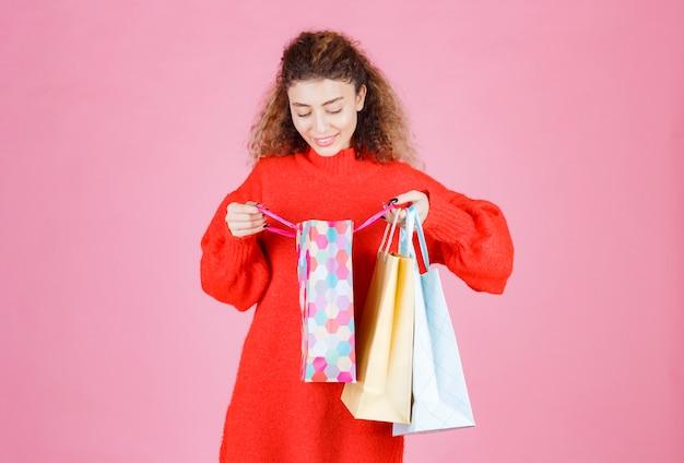 Femme ouvrant ses sacs colorés et vérifiant les produits.