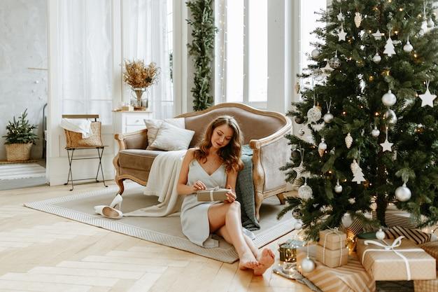 Une femme ouvre des cadeaux de noël chez elle dans un salon joliment décoré.