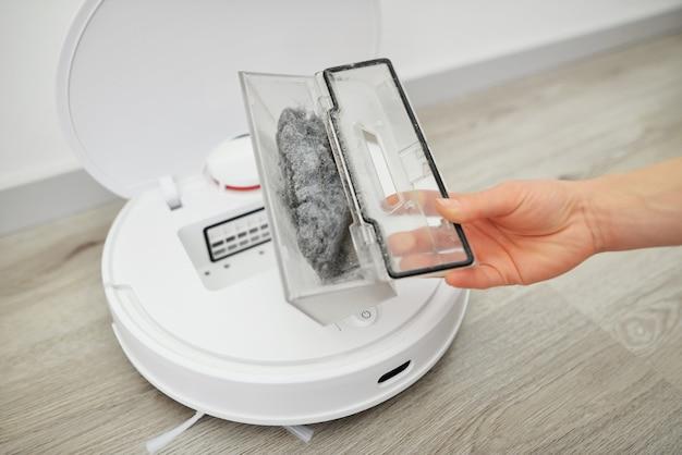 Femme ouvre le couvercle de l'aspirateur robot pour montrer un récipient en plastique transparent avec de petits déchets sur un plancher en bois en gros plan de la pièce bien éclairée.