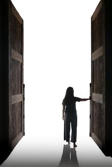 La femme ouvre la grande porte dans la lumière blanche
