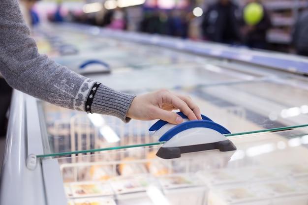 La femme ouvre la porte du compartiment réfrigérateur du supermarché
