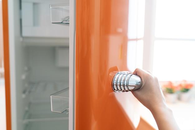 Femme ouvrir la porte du réfrigérateur dans la cuisine