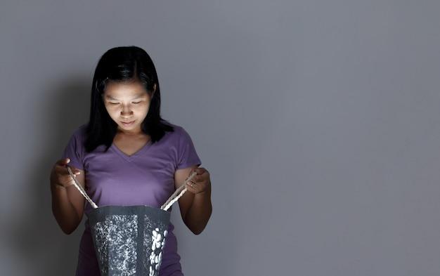 Femme ouvrir le sac à provisions avec quelque chose de léger à l'intérieur.