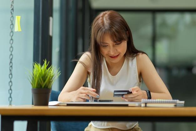 Une femme paie ses achats en ligne via un téléphone portable une femme tenant un smartphone et une carte de crédit