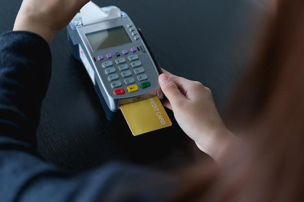 Femme paiement avec carte de crédit insérée dans la machine edc.