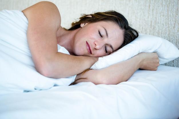 Femme paisible endormie dans son lit, couchée sur le ventre