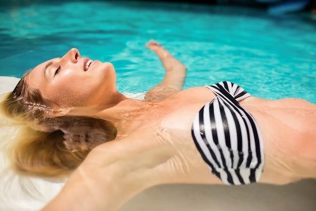 Femme paisible flottant dans la piscine avec les yeux fermés