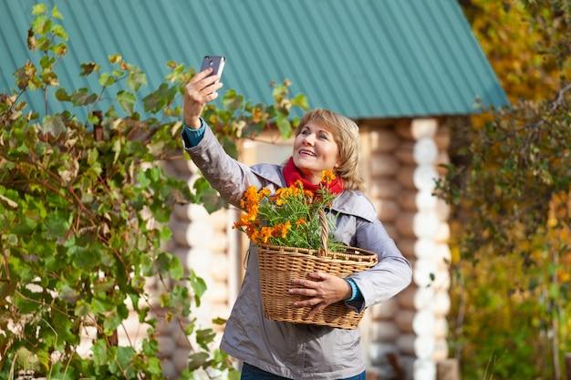 Une femme avec un panier est dans le jardin. une femme d'âge moyen en jeans et veste tient des fleurs contre les arbres d'automne. elle tient le téléphone