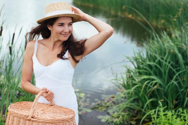 Femme avec panier pique-nique posant au bord du lac