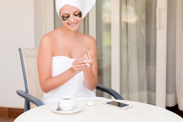 Femme avec des pansements oculaires applique de la crème sur ses mains