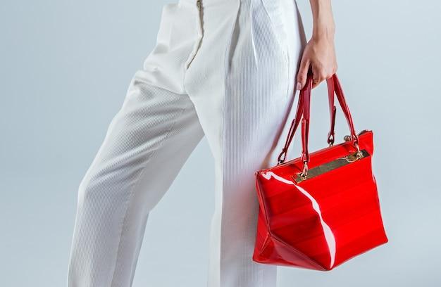 Femme en pantalon blanc et sac rouge