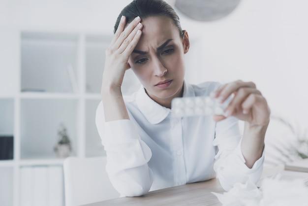 Une femme a un paquet de comprimés dans ses mains