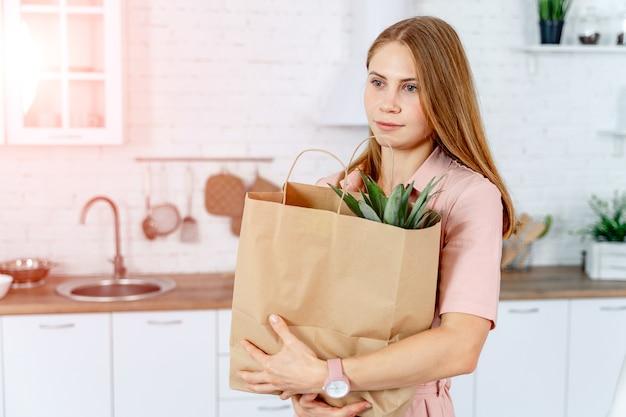 Femme avec le paquet d'épicerie dans les mains.