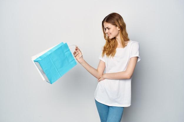 Femme avec des paquets en mains shopping divertissement amusant fond clair