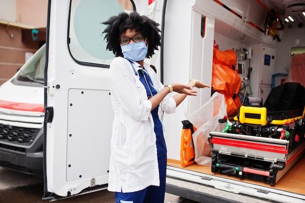 Femme paramédicale afro-américaine en masque facial debout devant la voiture d'ambulance