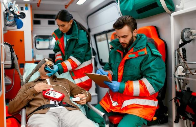 Une femme paramédicale en uniforme met un ventilateur avec de l'oxygène pour aider un patient âgé allongé avec un oxymètre de pouls sur une civière dans une ambulance moderne. un ambulancier masculin regarde le dossier d'un patient.