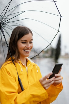 Femme avec parapluie à l'aide du téléphone mobile