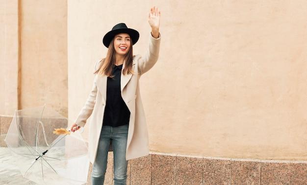 Femme avec parapluie ayant son bras levé avec copie espace