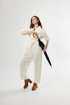 Femme en parapluie de costume blanc à la mode des mains
