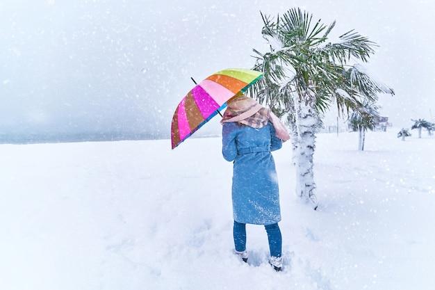 Femme avec un parapluie de couleur parmi les palmiers à feuilles persistantes couvertes de neige