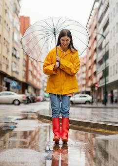 Femme avec parapluie debout sous la pluie longue vue