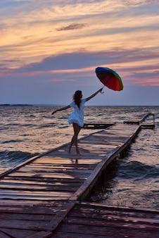 Femme avec parapluie en mains décolle de la jetée. les rêves deviennent réalité