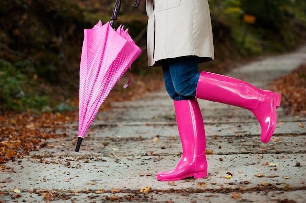 Femme avec parapluie portant des bottes en caoutchouc