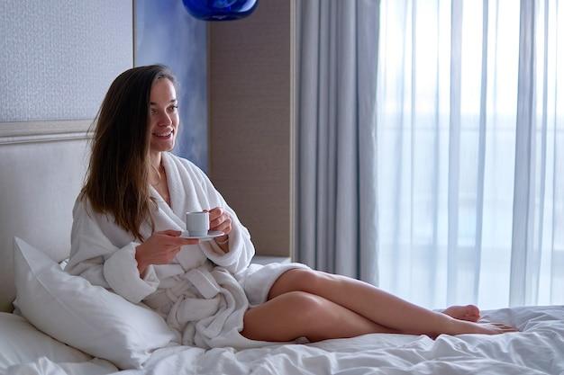 Femme paresseuse en peignoir allongé sur le lit et profiter d'un bon petit déjeuner avec une tasse de café aromatique pendant la détente dans une chambre confortable et confortable