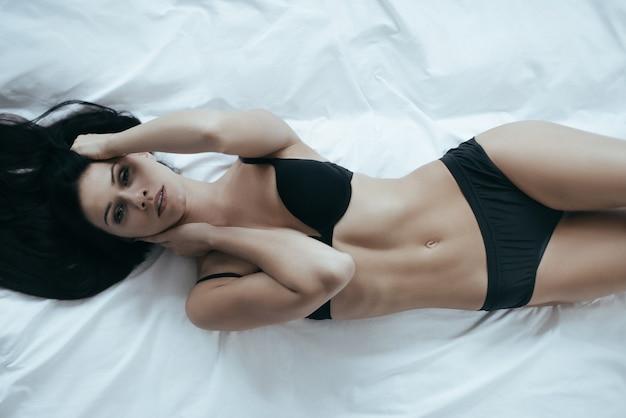 Femme parfaite. irrésistible jeune femme en sous-vêtements noirs posant de manière séduisante et regardant la caméra