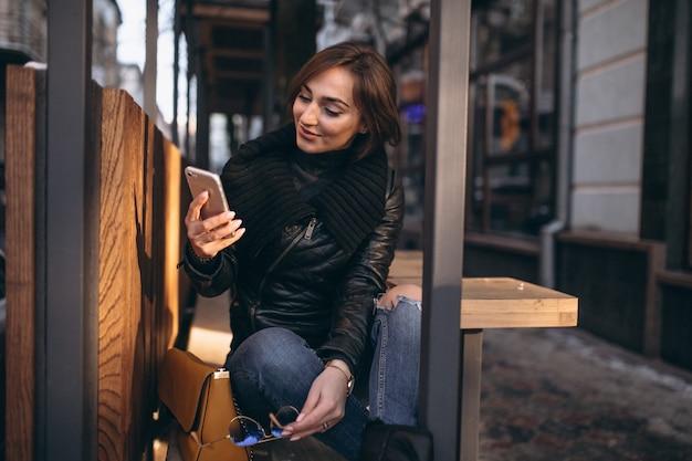 Femme parlant au téléphone et assis sur un banc dans la rue