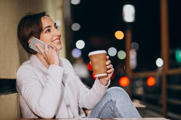 Femme parlant au téléphone et buvant du café dehors dans la rue la nuit